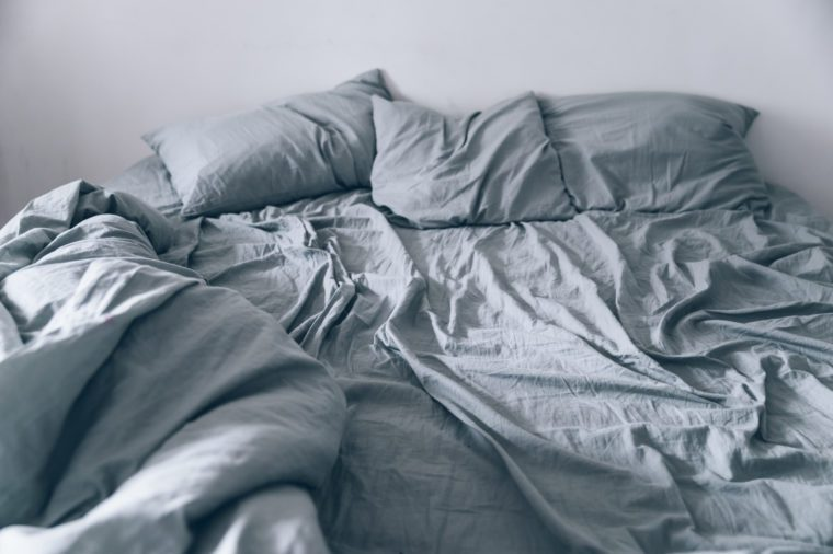 Empty messy gray bed with pillows and blanket