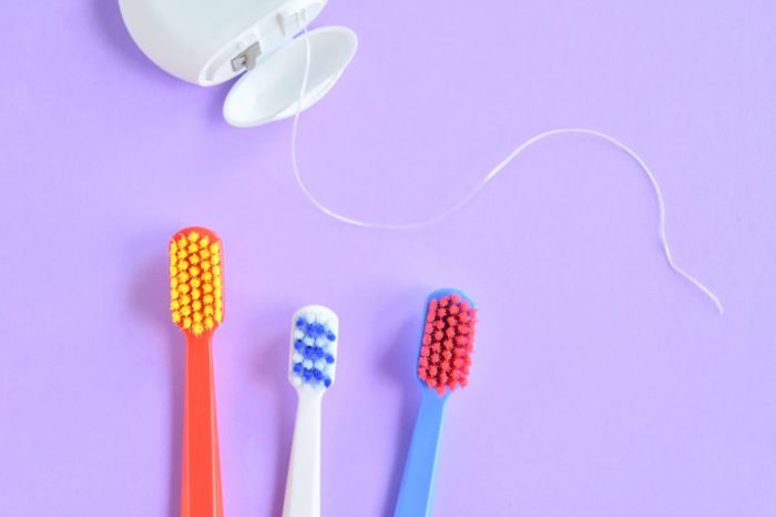 Colorful plastic toothbrushes and dental floss with selective focus on purple background with empty space for image or text. Toothbrush and hygienic dental thread for personal dental care