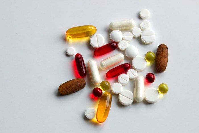 Background of assorted pharmaceutical capsules and medication in different colors, copy space