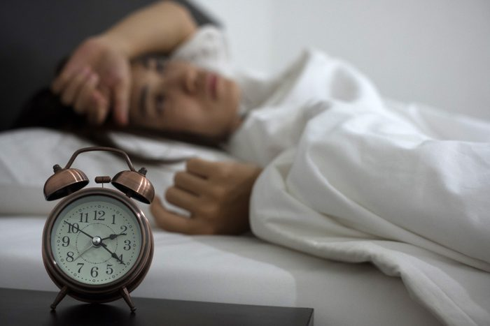 woman lying in bed with clock on night table