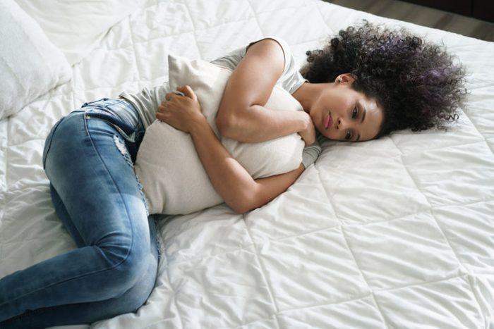 sad diverse woman pain miscarriage stomach ache