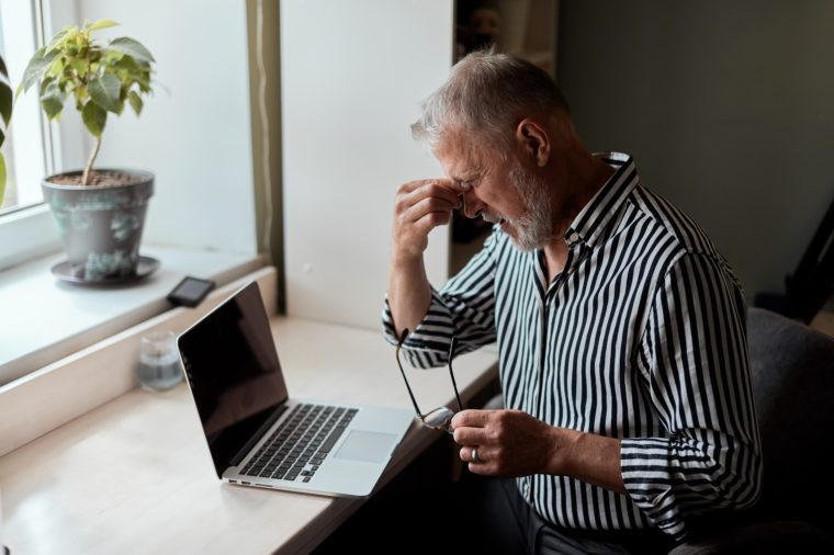 Photo Of Tired Mature bearded man sitting in front of laptop