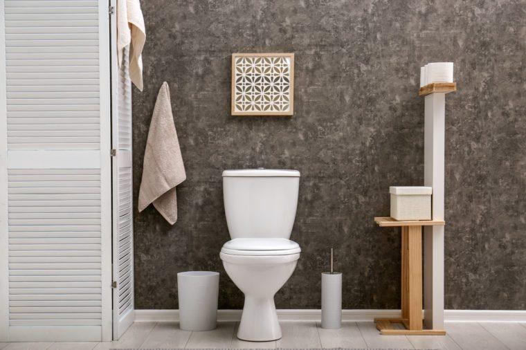 Toilet bowl near dark wall in modern bathroom interior
