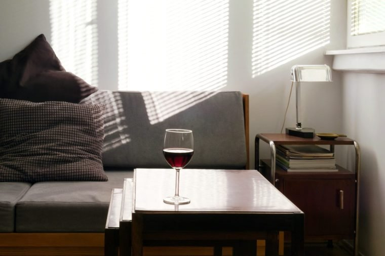 Home interior with glass of red wine on nesting tables, gray sofa and light beams on wall in background