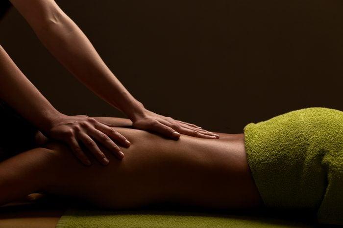 hands massaging woman's back