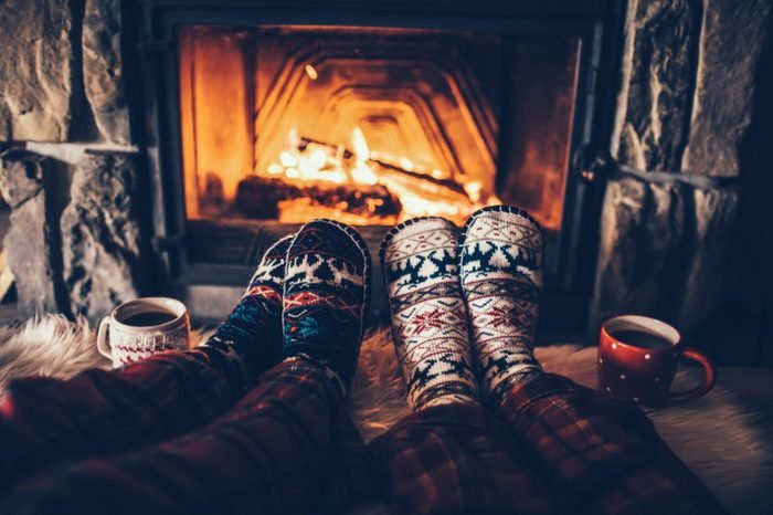 Feet in woollen socks by the Christmas fireplace. Couple sitting under the blanket, relaxes by warm fire and warming up their feet in woollen socks. Winter and Christmas holidays concept.