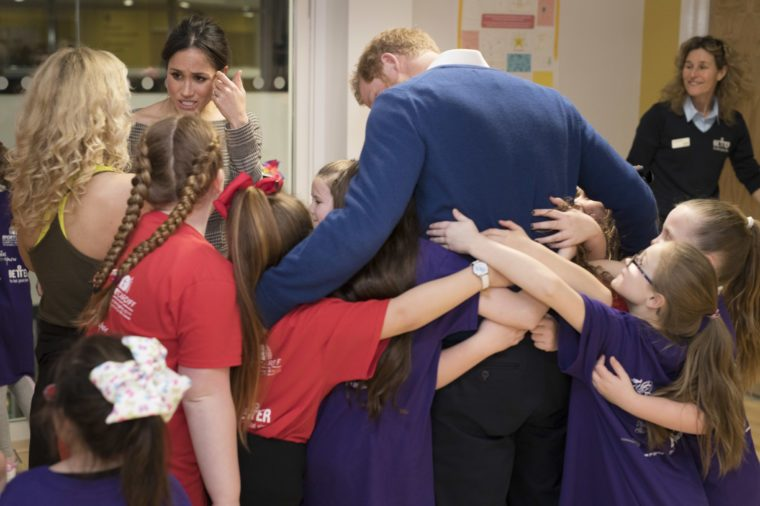 Prince Harry and Meghan Markle hug the children from at a street dance class during their visit to Star Hub