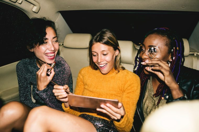 diverse women backseat of cab happy young