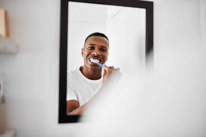 man brushing teeth in bathroom mirror