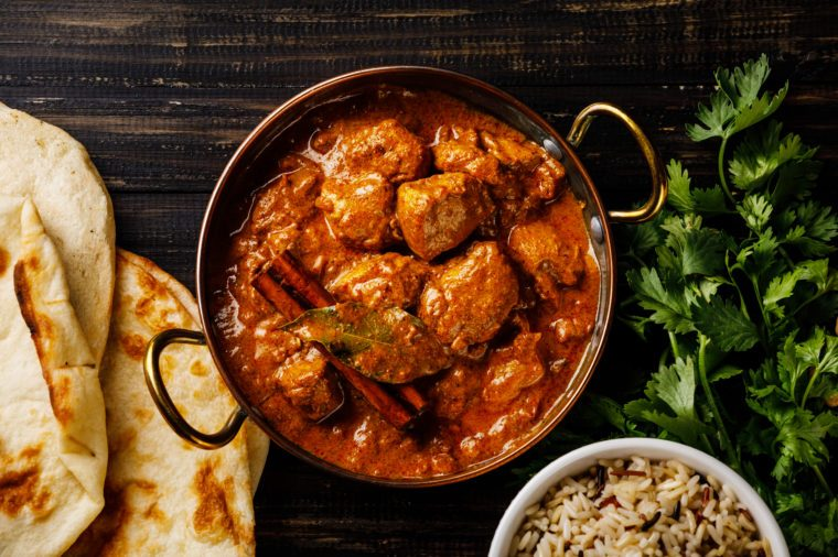 Chicken tikka masala spicy curry meat food Butter chicken with rice and naan bread on dark background close-up