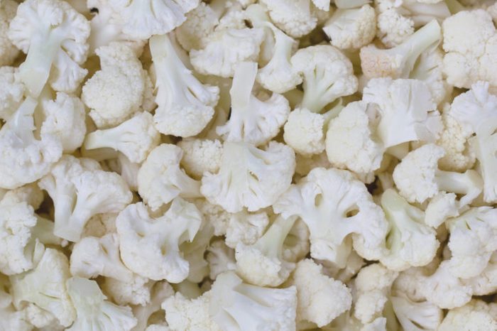 Small pieces of cauliflower in a real image. Heads, cauliflower inflorescence. Vintage of cauliflower. Fruits of cauliflower.