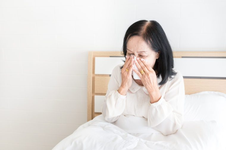 old asian female stay on white bed, influenza patient use tissue paper close her face, she cough and sneeze, elderly health care and health promotion, respiratory patient