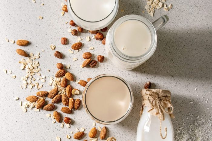 Variety of non-dairy vegan lactose free nuts and grain milk almond, hazelnut, coconut, rice, oat in glass bottles with ingredients above over white spotted background. Flat lay, space