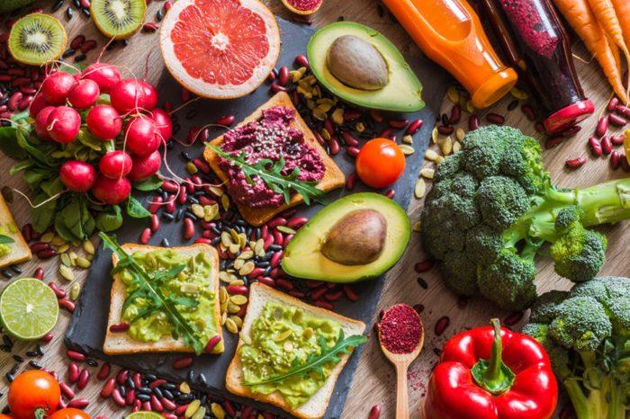 Healthy vegan food. Fresh vegetables on wooden background. Detox diet. Different colorful fresh juices.