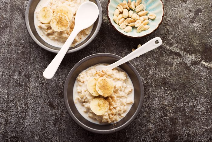 oatmeal and bananas in bowls with spoons