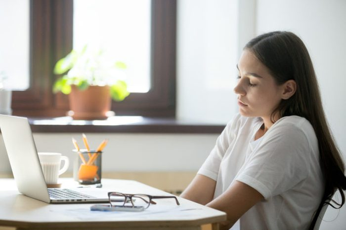 Female employee relaxing in her workplace, stretching her shoulders and back, keeping eyes closed . Woman taking a minute break from work, sitting near office window.