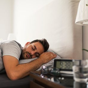man sleeping clock on nightstand do you need 8 hours of sleep