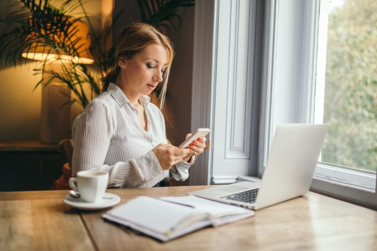 woman working and procrastinating on cell phone