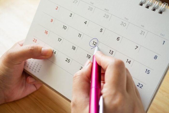 Hands circling a date on a calendar