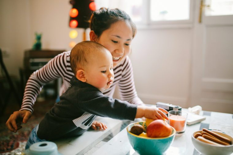 baby reaching for fruit with mother in kitchen