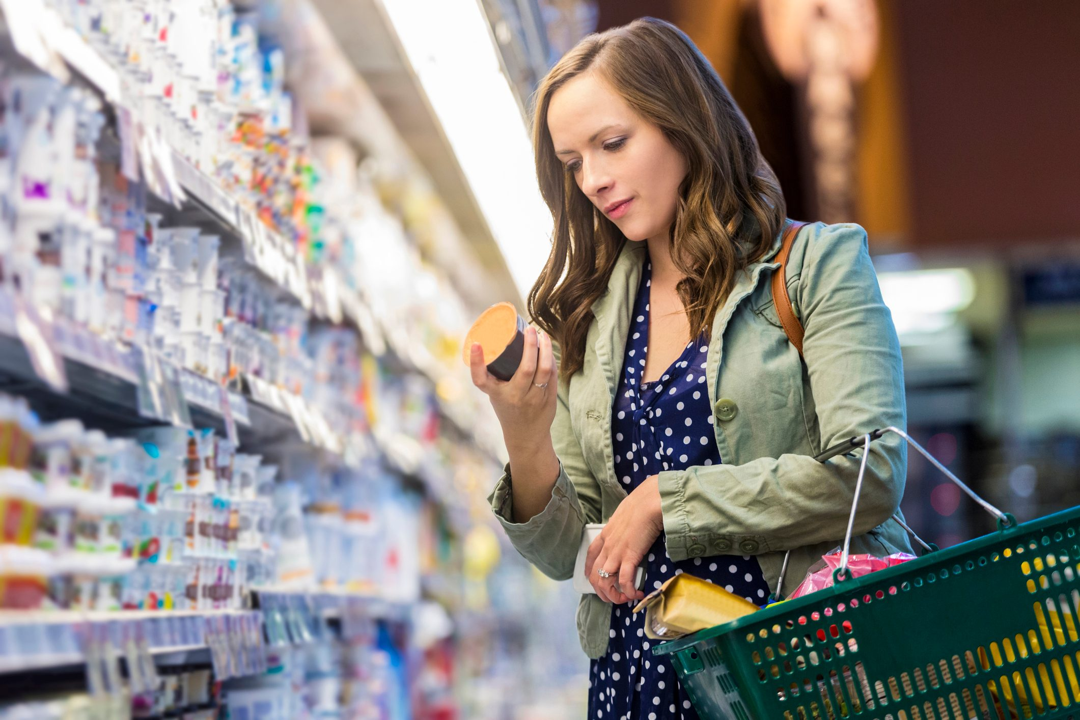 woman reading food label at grocery store