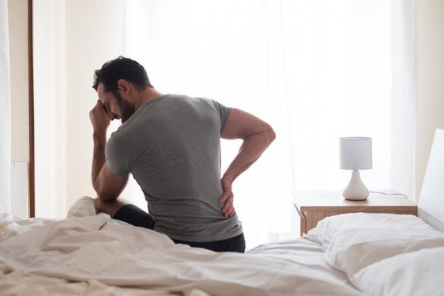 man waking up in the morning and feeling sore back pain