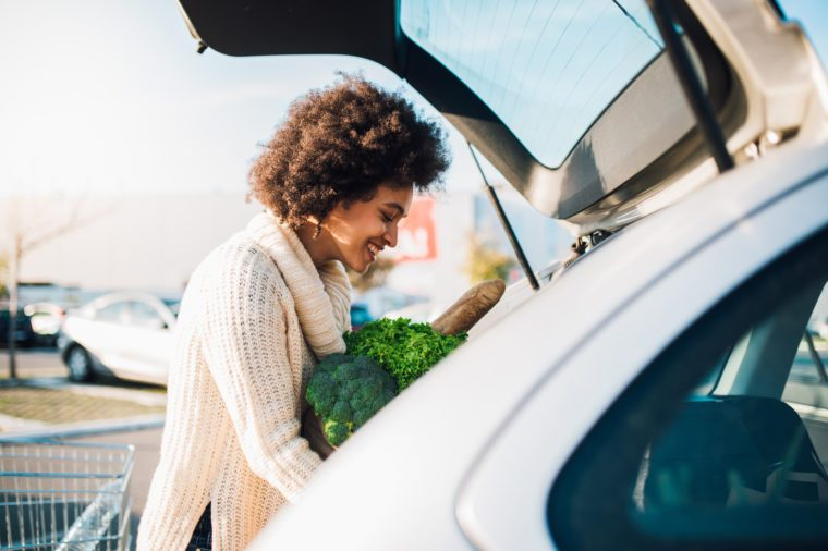 woman putting groceries into the trunk of car