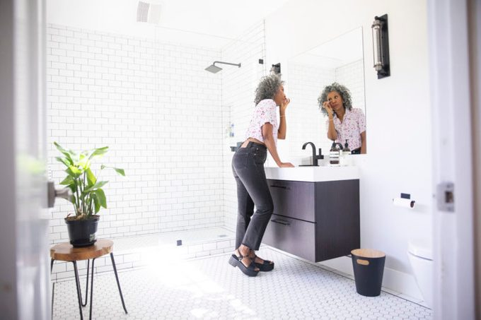 middle aged woman in the bathroom getting ready for the day