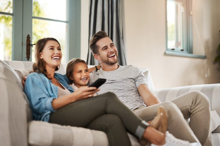 family watching tv together laughing