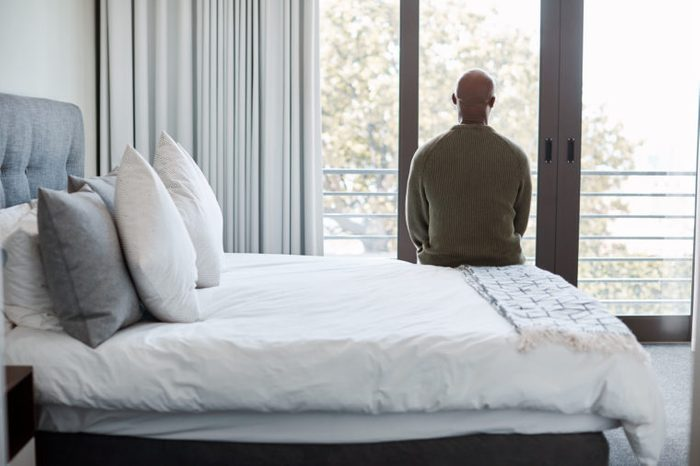 rear shot of man sitting on bed looking out window