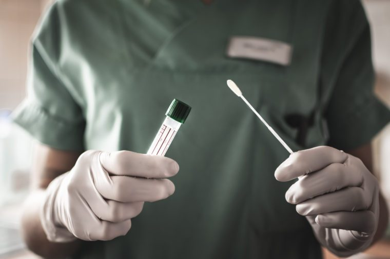 nurse or doctor holding test swab and test tube for coronavirus testing
