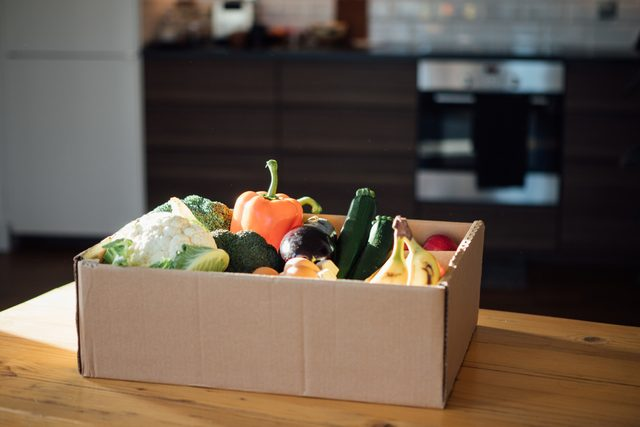 fresh groceries in cardboard box on kitchen table