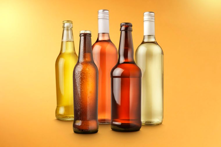 alcohol bottles on color background