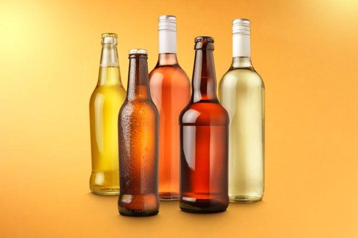 alcohol bottles on color background