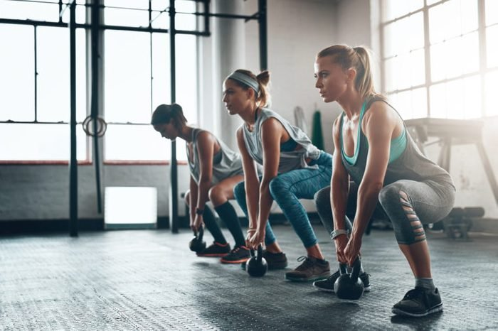 three woman doing a squat workout in the gym