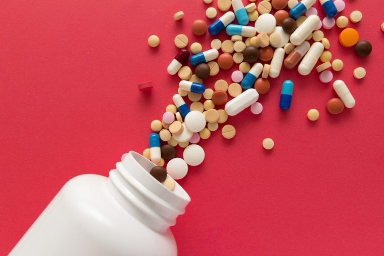 pills and pill bottle on red background