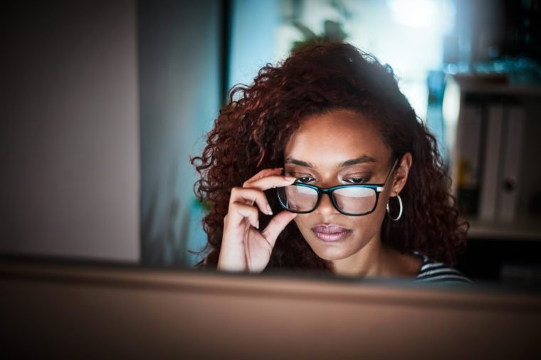 woman wearing anti blue light glasses working on computer late at night