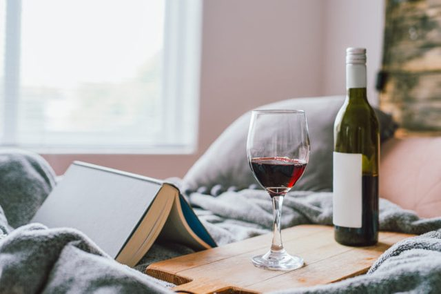 red wine bottle and glass with book on bed