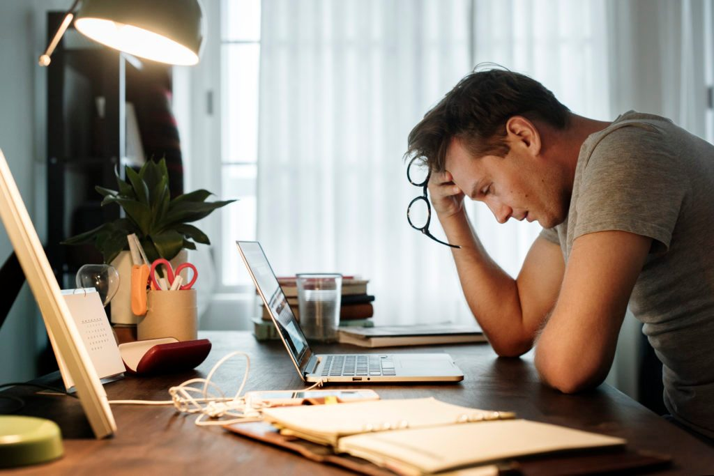 side view of man sitting at desk and struggling with work