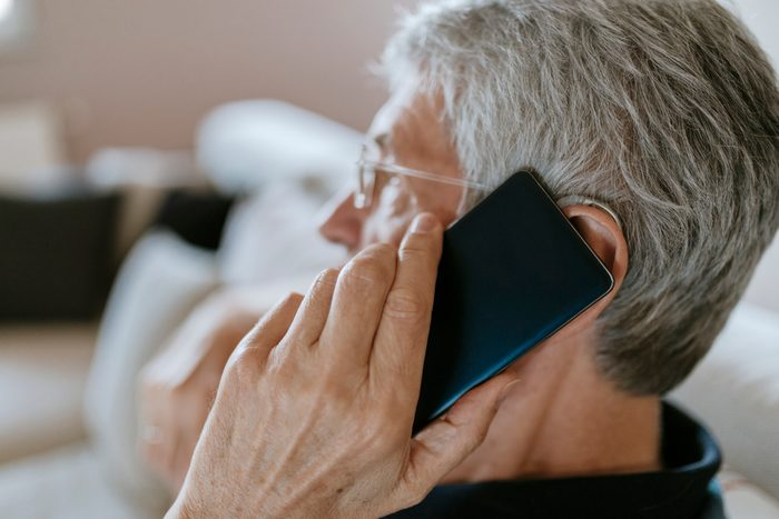 close up of man with phone to ear