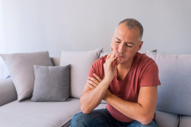 man suffering from toothache at home