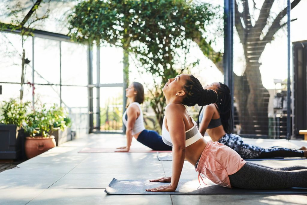 group of woman practicing yoga and meditation outside
