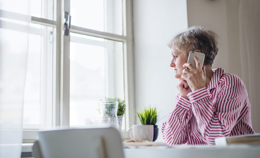 older woman sitting at home talking on the phone