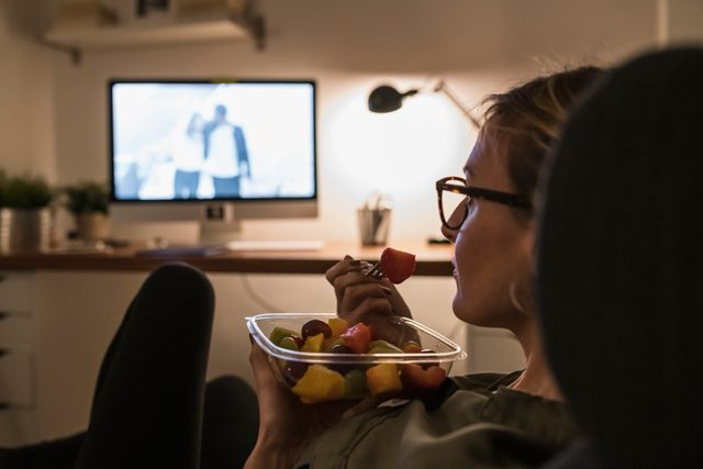 woman eating a snack and watching a movie at home after work