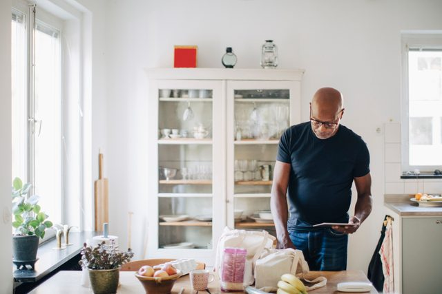 man sorting through groceries in kitchen