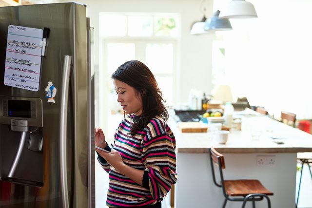 woman looking in fridge to see what she needs from the grocery store