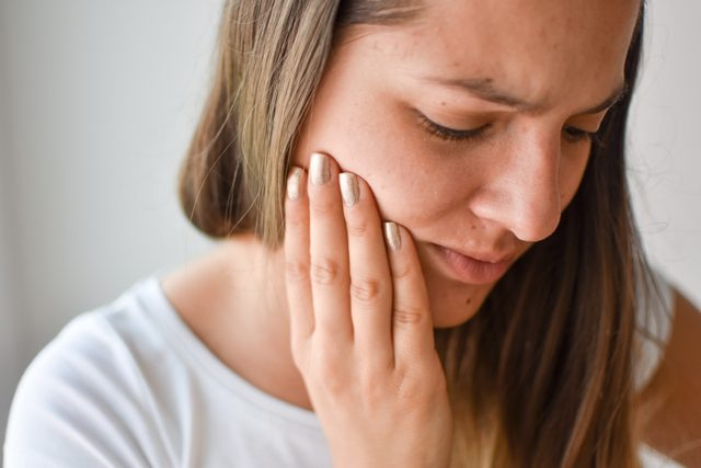 young woman suffering from jaw pain
