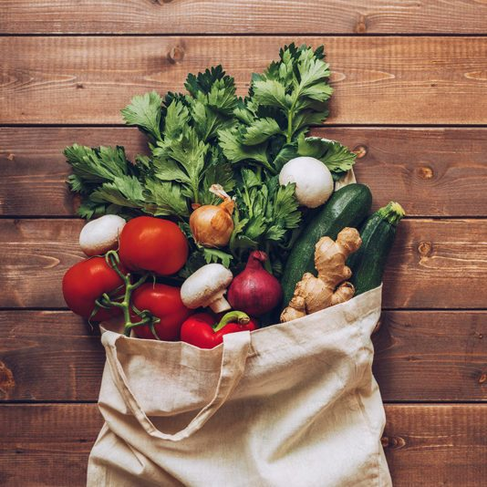 fresh produce in grocery bag overhead