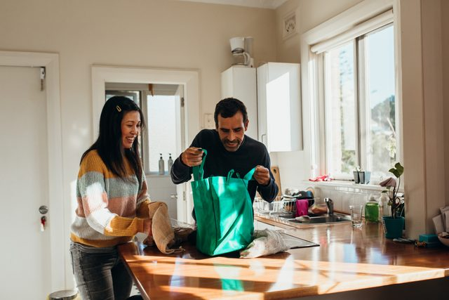 couple unpacking groceries in kitchen