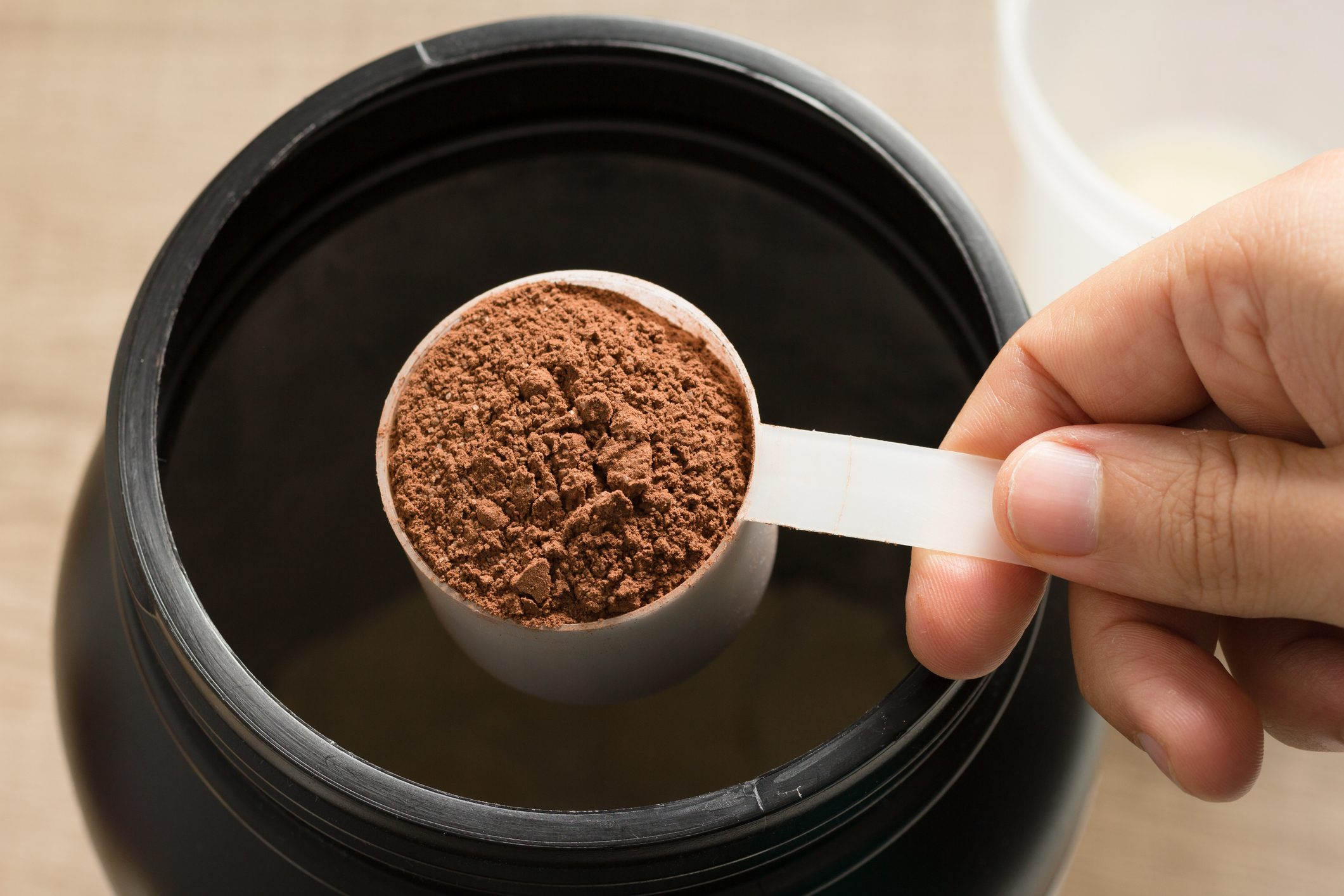 overhead shot of man holding a scoop of protein powder